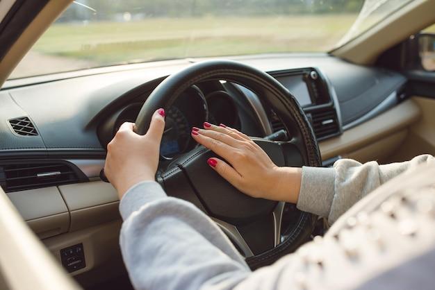 도로에서 차를 운전하는 사람의 손입니다.