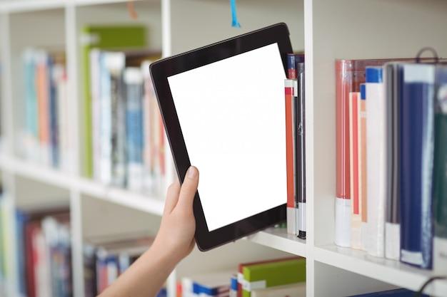 図書館の本棚にデジタルタブレットを維持する学生の手