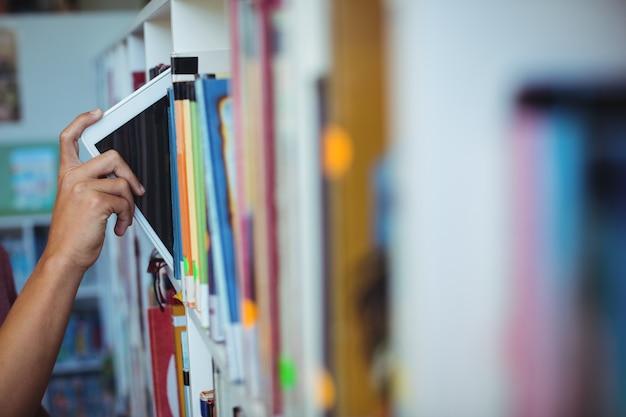 도서관의 책장에 디지털 태블릿을 유지하는 학생의 손