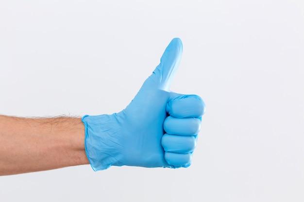 흰색 배경에 고립 된 확인 기호를 보여주는 파란색 의료 장갑에 외과 의사의 손