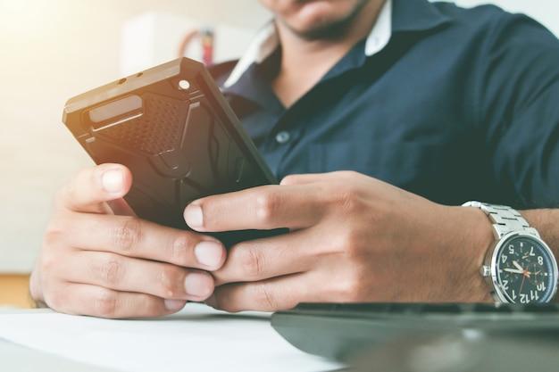 スマートフォンを持っている日焼け肌の手。ビジネスとワーキングオフィスのコンセプト。仕事のコンセプト。スマートフォンを使用しています。スマートフォンと通信します。