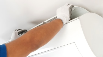 Hand of technician cleaning air conditioner in house