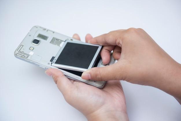 Рука техника или инженера включает смартфон, чтобы заменить разряженный аккумулятор