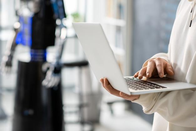 Рука подростка с ноутбуком, разрабатывающего новое программное обеспечение, работая над технологическим проектом на фоне робота в колледже