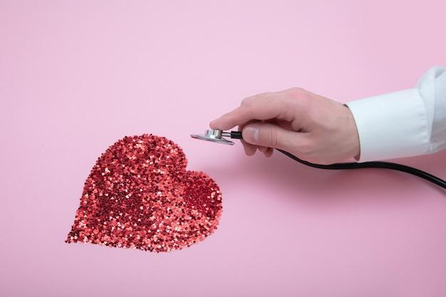 Statoscope를 가진 의사의 손은 모양에 많은 곱슬 장식 조각으로 만든 심장을 듣습니다.