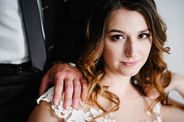 신랑의 손을 어깨에 얹은 신부. 결혼식. 남자는 여자를 안아.