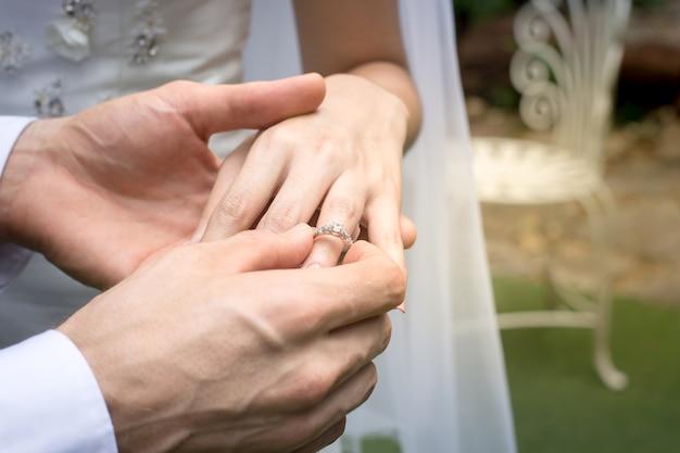 新郎新婦の手は結婚式の花嫁を身に着けている