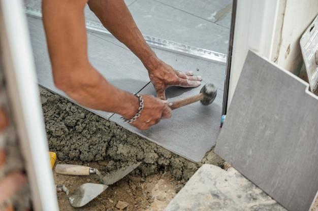 Рука укладывает плитку и молотком сбивает гранитную плитку на пол