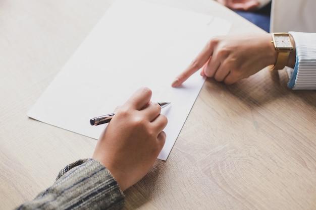ホワイトペーパーに署名するビジネス契約をしている2人の女性の手