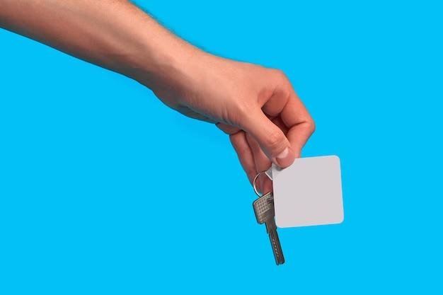 未知の男性の手が空白の白い四角いプラスチックの鍵で鍵を握っています