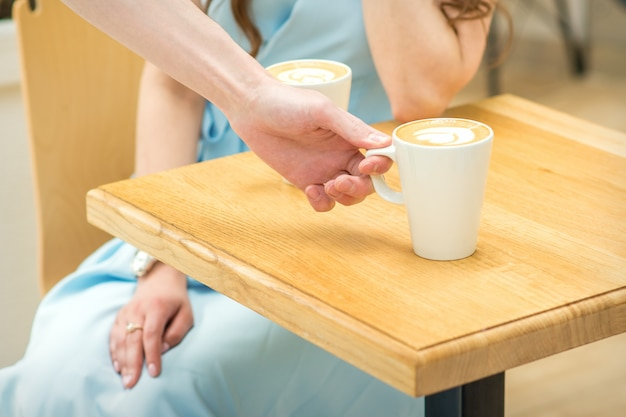 Рука официанта ставит чашку кофе латте на деревянный стол в кафе