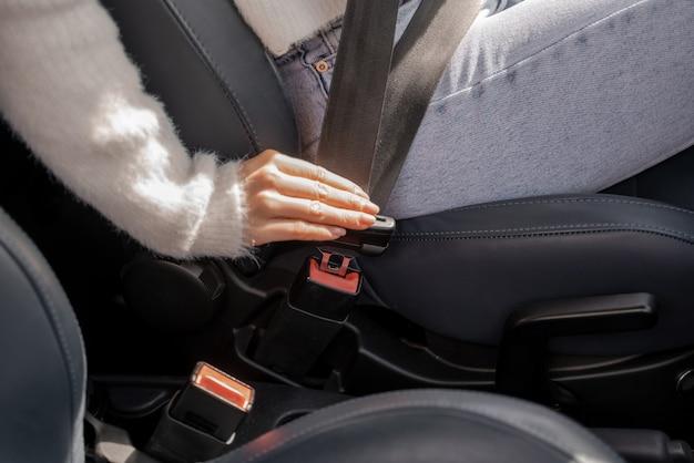 女性の手が車のシートベルトを締めます。ビューを閉じます。車の運転の概念