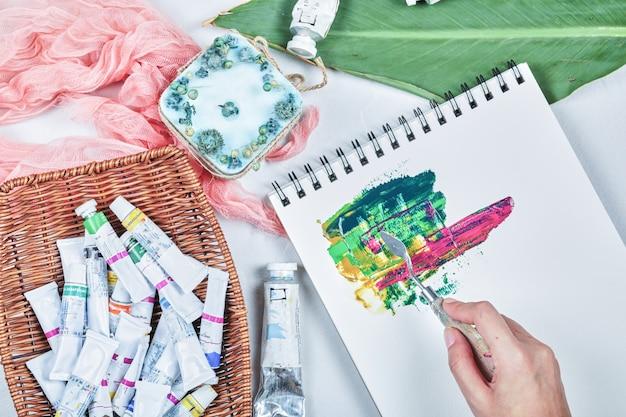 油絵の具で絵を描く女性の手。
