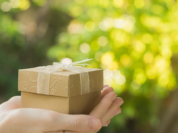 女性の手は、ボケ味の背景にクリスマスギフトボックスを保持します。