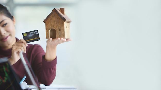 コピースペースのあるおもちゃの家を持っている女性の手。クレジットで家を提出する