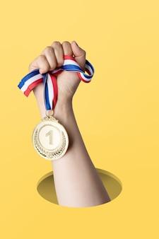 黄色の背景に金メダルを保持している女性の手。賞と勝利の概念。コピースペース
