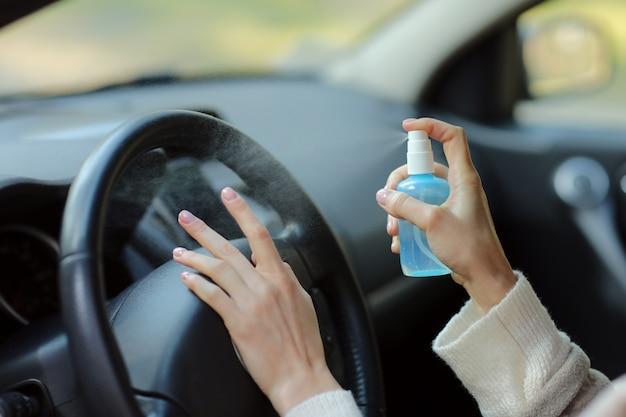 Рука женщины распыляет спирт, дезинфицирующее средство в машине, безопасность, предотвращает заражение вирусом covid 19, коронавирусом, загрязнением микробами или бактериями. алкоголь дезинфицирующее средство, гигиена концепции.