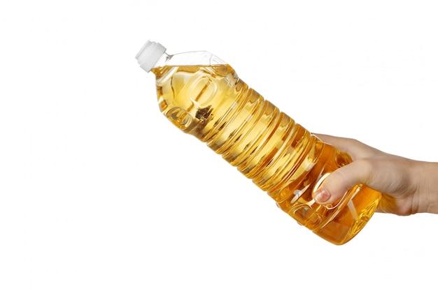 ペットボトルから食用油を注ぐ女性の手。白い背景で隔離されました。