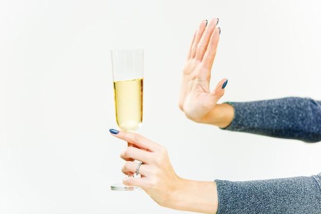 Рука женщины, отказывающейся от стекла с алкогольным напитком, на белом фоне. концепция без алкоголя