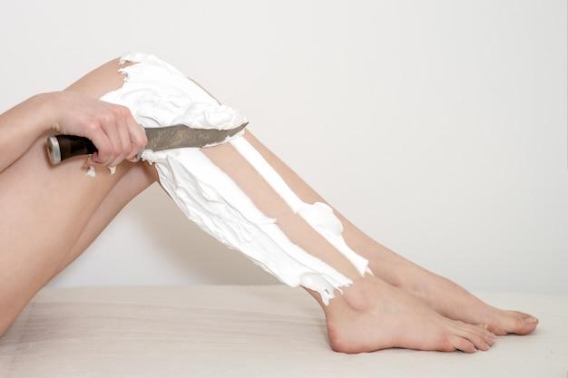 여자의 손은 다리를 면도합니다.