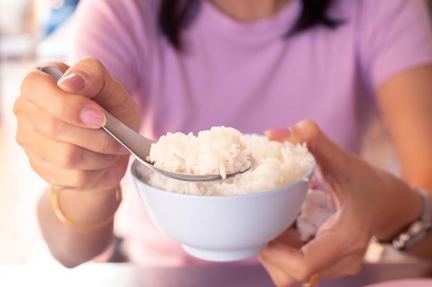 여자 사용 숟가락의 손을 그릇에 쌀을 유지