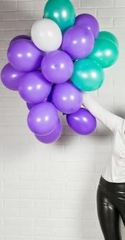 Рука женщины с цветными воздушными шарами в помещении