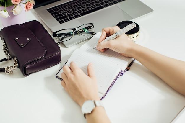 ノートパソコン、メガネ、花のポットとオフィスのデスクトップに配置された空のメモ帳で書く女性の手