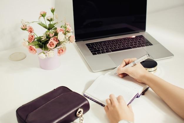 ノートパソコン、花のポットでオフィスのデスクトップに配置された空のメモ帳に書く女性の手