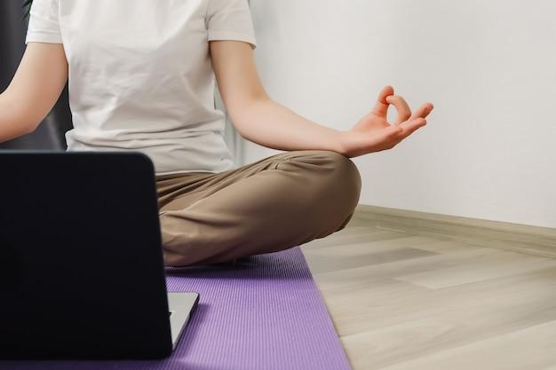 바닥에 앉아있는 동안 연꽃 포즈를 취하는 여성의 손