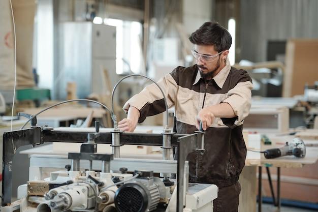 Рука рабочего или инженера современной фабрики по производству мебели, поворачивая ручку промышленного станка во время фиксации заготовки