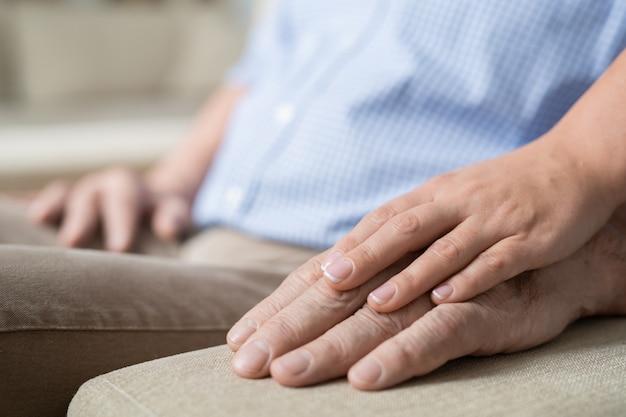 ベージュの柔らかいソファのハンドルに彼女の年長の父親のそれについて若い愛情深く注意深い女性の手