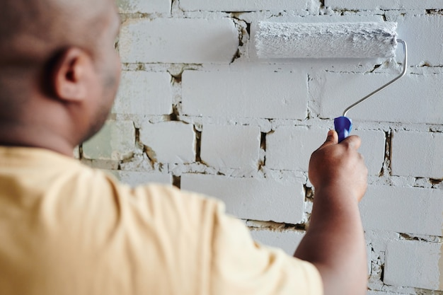 Рука молодого африканца в бежевой футболке, держащего валик, стоя перед кирпичной стеной и раскрашивающая ее в белый цвет