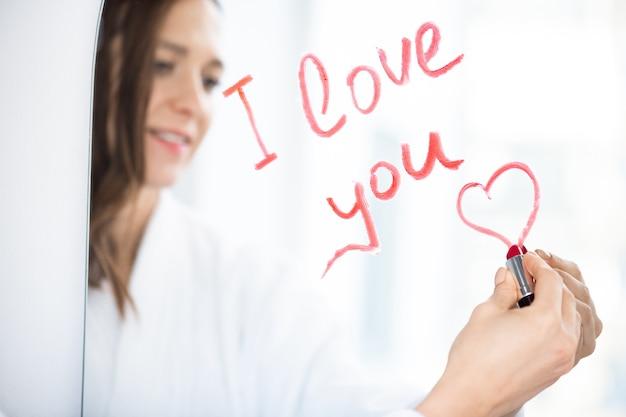 愛のメッセージを書き、鏡に赤または深紅の口紅で小さなハートを描く若い好色なブルネットの女性の手