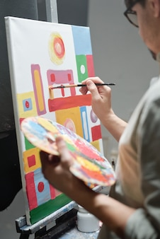 예술 스튜디오에서 캔버스에 새 그림을 통해 작업하는 동안 페인트 브러시를 사용하는 동안 색상 팔레트를 들고 젊은 예술가의 손