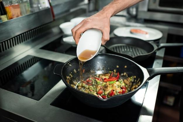 요리하는 동안 녹색 완두콩, 다진 호박, 샴피뇽, 양파, 고추를 넣은 프라이팬에 사과 주스를 붓는 젊은 요리사의 손