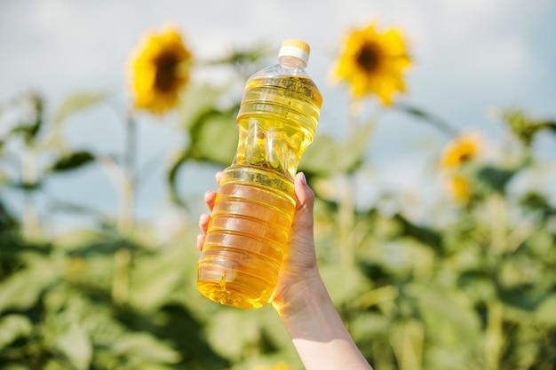 큰 노란색 꽃이 있는 녹색 식물에 대해 신선한 해바라기 기름이 든 플라스틱 병을 들고 있는 젊은 현대 여성 농부의 손