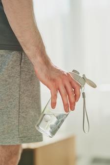Рука молодого современного спортсмена, держащего бутылку воды, отдыхая после тяжелой тренировки дома или в тренажерном зале утром