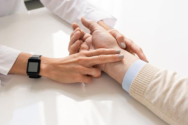 Рука молодого врача с умными часами на запястье пожилого пациента во время процедуры проверки пульса и медицинской консультации