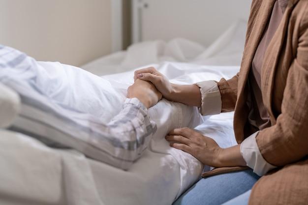 現代の病室のベッドに横たわっているパジャマで彼女の病気の友人のそれを保持しているカジュアルウェアの若い強調女性の手
