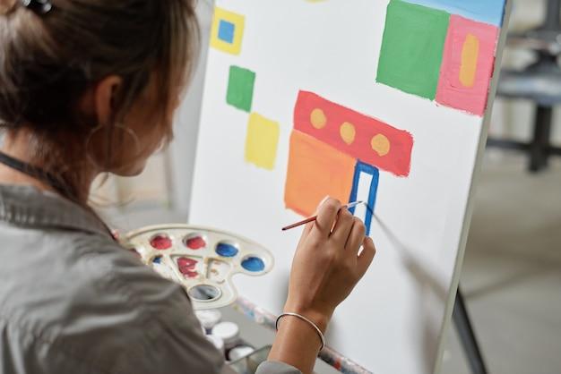 イーゼルのそばに座って、紙に絵筆で絵を描いている間、カラーパレットを保持している若い女性アーティストの手