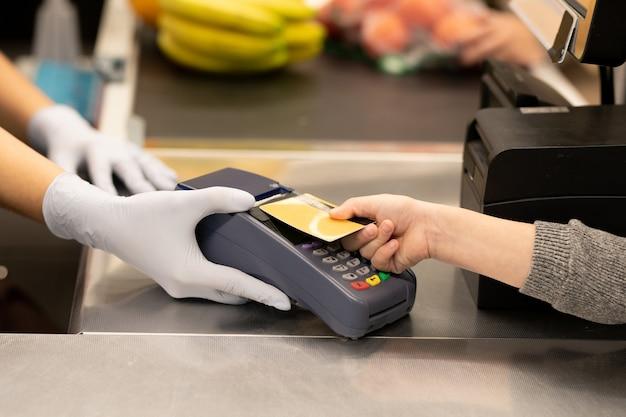 슈퍼마켓 카운터 위에 장갑을 낀 계산원이 들고 있는 결제 단말기 화면에 신용 카드를 들고 있는 젊은 여성 소비자의 손