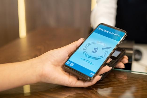 리셉션 카운터에 서 있는 결제 기계를 통해 화면에 온라인 뱅킹 페이지가 있는 스마트폰을 들고 있는 젊은 여성 여행자의 손