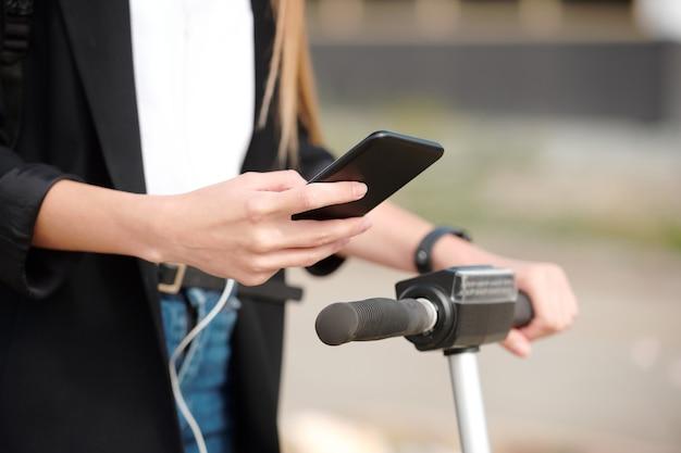 출근길에 전기 스쿠터의 손잡이를 잡고 재생 목록을 스크롤하는 모바일 가제트를 가진 젊은 여성의 손