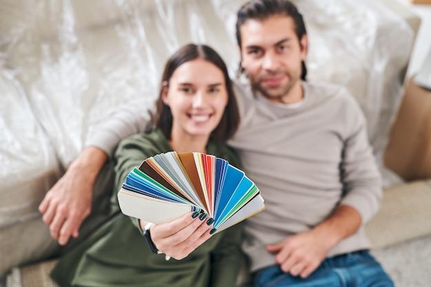 Рука молодой счастливой женщины показывает цветовую палитру, сидя рядом со своим мужем на полу своей новой квартиры или дома