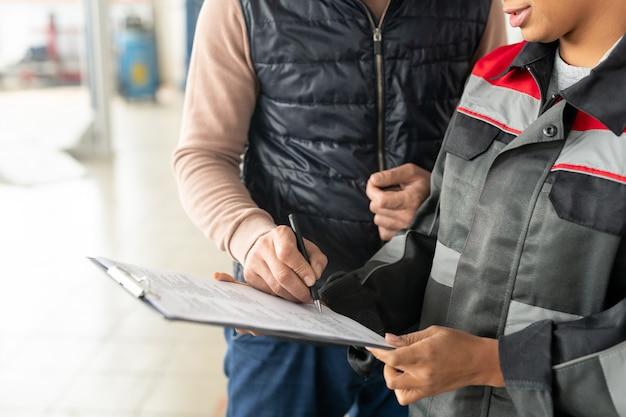 Рука молодого мужчины-клиента службы ремонта автомобилей, ставящая подпись в документе после ремонта автомобиля, стоя рядом с женским техником
