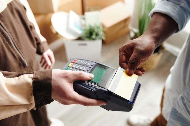 결제 단말기를 들고 있는 작업복을 입은 청년의 손, 아프리카 남성은 신용카드로 서비스를 적재하고 배달하는 비용을 지불합니다.