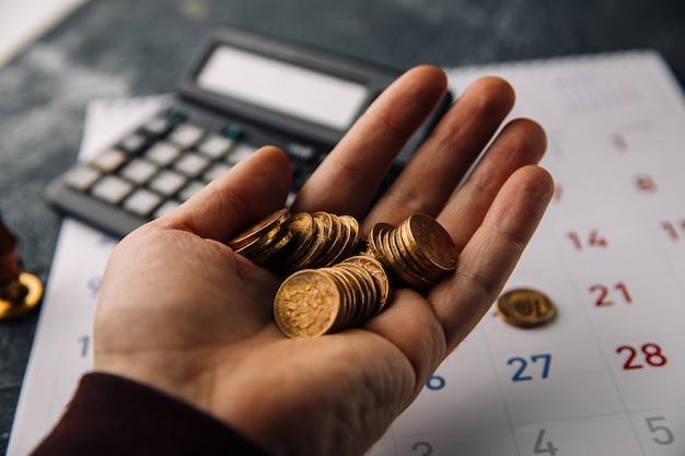젊은 남자의 손에 동전, 사업 투자 기금에 돈을 절약하기위한 개념을 잡고있다.