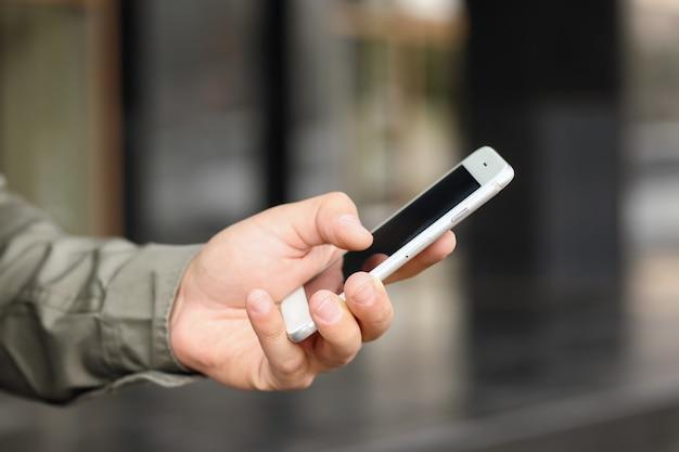 屋外で彼の携帯電話を使用して若い男の手