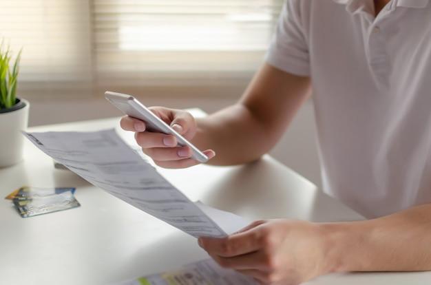 홈 오피스에서 책상에 가족 예산 비용 청구서와 함께 온라인 스캔 및 지불을 위해 모바일 스마트 폰을 사용하는 젊은 남자의 손, 돈 비용 절약, 투자, 사업 금융, 비용 개념 계획
