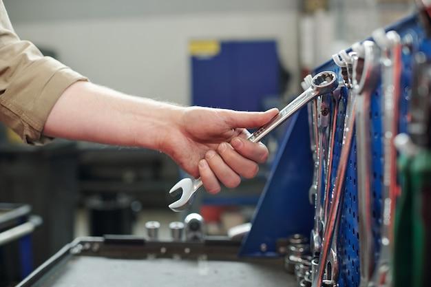 彼の仕事をする前にフックにぶら下がっているレンチの1つを取る若い技術者、整備士または修理工の手